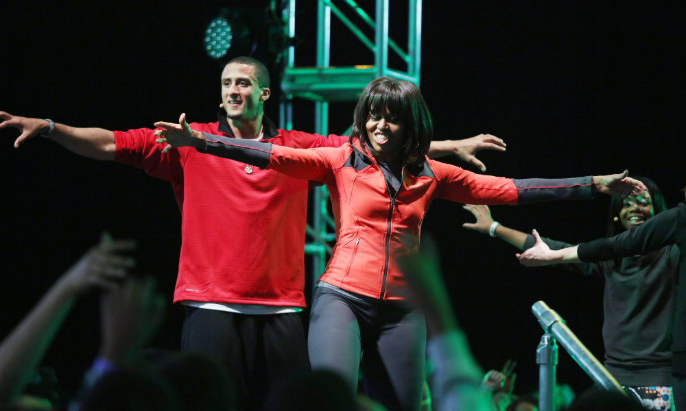"CHICAGO,IL - FEBRUARY 28:  First lady Michelle Obama (R) dances with San Francisco 49ers quarterback Colin Kaepernick during a debut of a school exercise program February 28, 2013 in Chicago, Illinois. Obama unveiled a new initiative called ""Let's Move Active Schools"" to help schools create a physical activity programs for students.  (Photo by Tasos Katopodis/Getty Images) ORG XMIT: 162869474 ORIG FILE ID: 162851170"